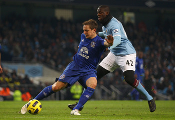 MANCHESTER, ENGLAND - DECEMBER 20:  Phil Jagielka of Everton holds off a challenge from Ya Ya Toure of Manchester City during the Barclays Premier League match between Manchester City and Everton at City of Manchester Stadium on December 20, 2010 in Manch