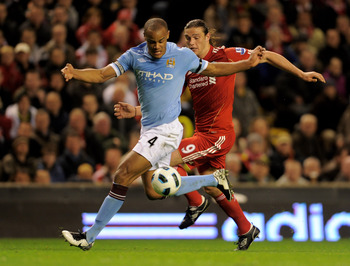 LIVERPOOL, ENGLAND - APRIL 11:  Andy Carroll of Liverpool competes with Vincent Kompany of Manchester City during the Barclays Premier League match between Liverpool and Manchester City at Anfield on April 11, 2011 in Liverpool, England.  (Photo by Michae