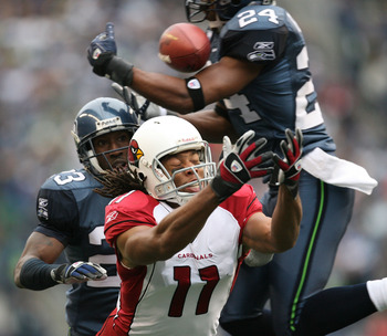 SEATTLE - DECEMBER 9:  Wide receiver Larry Fitzgerald #11 of the Arizona Cardinals fights to make a catch against Deon Grant #24 of the Seattle Seahawks at Qwest Field December 9, 2007 in Seattle, Washington. The ball fell incomplete. (Photo by Otto Greul