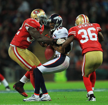 LONDON, ENGLAND - OCTOBER 31:  Jabar Gaffney #10 of Denver Broncos is tackled by Patrick Willis #52 and Shawntae Spencer #36 of San Francisco 49ers during the NFL International Series match between Denver Broncos and San Francisco 49ers at Wembley Stadium