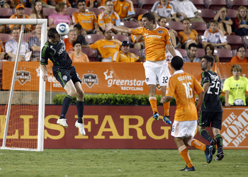 HOUSTON - JULY 30:  Nate Jaqua #21 of the Seattle Sounders gets his head on the ball but can't direct on goal as Bobby Boswell #32 of the Houston Dynamo looks on at Robertson Stadium on July 30, 2011 in Houston, Texas.  (Photo by Bob Levey/Getty Images)