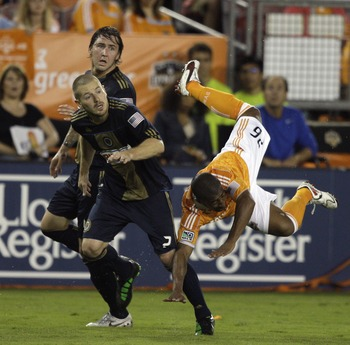HOUSTON, TX - MARCH 19:  Corey Ashe #26 of the Houston Dynamo takes a dive against Jordan Harvey #2 of the Philadelphia Union during a game at Robertson Stadium on March 19, 2011 in Houston, Texas.  (Photo by Bob Levey/Getty Images)