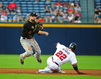 ATLANTA - JULY 26: Neil Walker #18 of the Pittsburgh Pirates turns a double play against Jason Heyward #22 of the Atlanta Braves at Turner Field on July 26, 2011 in Atlanta, Georgia. (Photo by Scott Cunningham/Getty Images)
