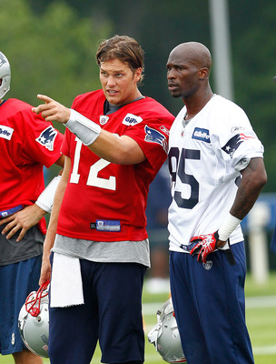 FOXBOROUGH, MA  - JULY 29:  Tom Brady #12 and Chad Ochocinco #85 of the New England Patriots chats during the afternoon session of training camp at Gillette Stadium on July 29, 2011 in Foxborough, Massachusetts.  (Photo by Jim Rogash/Getty Images)