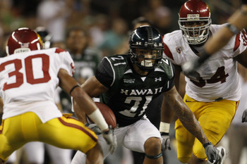 HONOLULU - SEPTEMBER 2:  Kealoha Pilares #21of the University of Hawaii Warriors  tries to avoid the USC defense during second half action at Aloha Stadium September 2, 2010 in Honolulu, Hawaii. (Photo by Kent Nishimura/Getty Images)