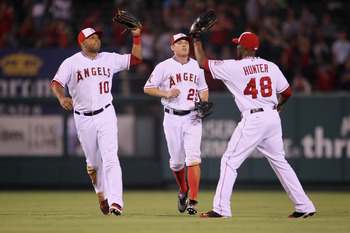 ANAHEIM, CA - JULY 04:  (L-R) Vernon Wells #10, Peter Bourjos #25 and Torii Hunter #48 of the Los Angeles Angels of Anaheim celebrate following their teams victory over the Detroit Tigers at Angel Stadium of Anaheim on July 4, 2011 in Anaheim, California.
