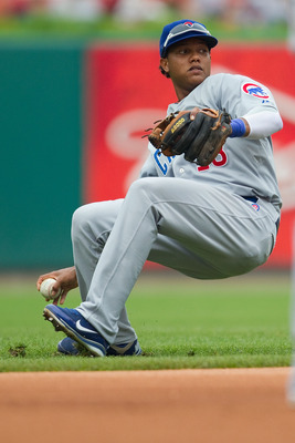 ST. LOUIS, MO - JULY 30: Starlin Castro #13 of the Chicago Cubs attempts to throw to first base against the St. Louis Cardinals at Busch Stadium on July 30, 2011 in St. Louis, Missouri.  (Photo by Dilip Vishwanat/Getty Images)