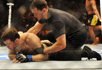 PHILADELPHIA - AUGUST 08:  (Bottom) Forrest Griffin on the ground after being defeated by Anderson Silva during their light heavyweight bout at UFC 101: Declaration at the Wachovia Center on August 8, 2009 in Philadelphia, Pennsylvania.  (Photo by Jon Kop