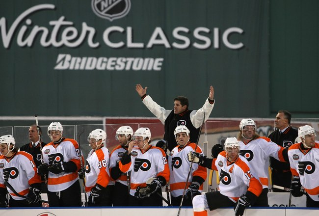 BOSTON - JANUARY 01:  Peter Laviolette, head coach of the Philadelphia Flyers, reacts during the game against the Boston Bruins during the 2010 Bridgestone Winter Classic at Fenway Park on January 1, 2010 in Boston, Massachusetts. The Boston Bruins defeat