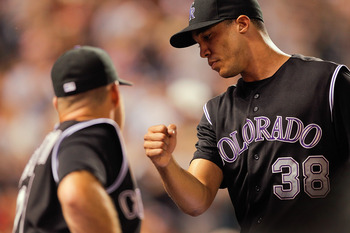 DENVER, CO - JULY 19:  Starting pitcher Ubaldo Jimenez #38 of the Colorado Rockies is greeted by teammate Ty Wigginton #21 after being taken out in the seventh inning against the Atlanta Braves at Coors Field on July 19, 2011 in Denver, Colorado.  (Photo