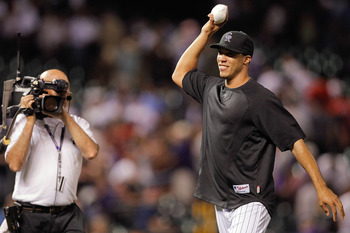 DENVER, CO - JULY 19:  Ubaldo Jimenez #38 of the Colorado Rockies jokes with teammates as he walks off the field at Coors Field on July 19, 2011 in Denver, Colorado. The Rockies defeated the Braves 12-3. (Photo by Justin Edmonds/Getty Images)