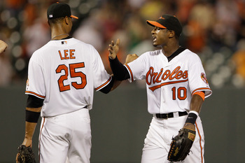 BALTIMORE, MD - JULY 23: Derrek Lee #25 and teammate Adam Jones #10 of the Baltimore Orioles celebrate the Orioles 3-2 win over the Los Angeles Angels of Anaheim at Oriole Park at Camden Yards on July 23, 2011 in Baltimore, Maryland.  (Photo by Rob Carr/G
