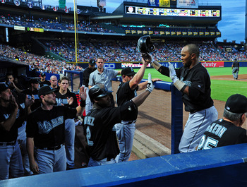 ATLANTA - JULY 30: Emilio Bonifacio #1 of the Florida Marlins is congratulated by teammates after scoring against the Atlanta Braves at Turner Field on July 30, 2011 in Atlanta, Georgia. (Photo by Scott Cunningham/Getty Images)