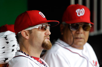 WASHINGTON, DC - JULY 28: Jonny Gomes #30 and coach Pat Corrales #39 of the Washington Nationals sit together before the start of the Nationals game against the Florida Marlins at Nationals Park on July 28, 2011 in Washington, DC. (Photo by Rob Carr/Getty