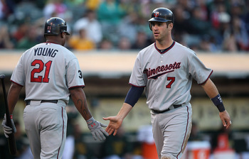OAKLAND, CA - JULY 29:  Joe Mauer #7 of the Minnesota Twins celebrates with Delmon Young #21 after scoring on a Jason Kubel double against the Oakland Athletics at O.co Coliseum on July 29, 2011 in Oakland, California.  (Photo by Jed Jacobsohn/Getty Image