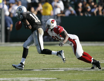 Arizona cornerback Antrel Rolle pressures Oakland receiver Randy Moss to drop the ball as the Oakland Raiders defeated the Arizona Cardinals by a score of 22 to 9 at McAfee Coliseum, Oakland, California, October 22, 2006. (Photo by Robert B. Stanton/NFLPh
