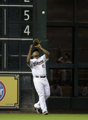 HOUSTON - JULY 15:  Left fielder Carlos Lee #45 of the Houston Astros makes a catch near the wall against the PIttsburgh Pirates at Minute Maid Park on July 15, 2011 in Houston, Texas.  (Photo by Bob Levey/Getty Images)