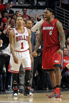 CHICAGO, IL - MAY 26:  Derrick Rose #1 of the Chicago Bulls looks on dejected as LeBron James #6 of the Miami Heat celebrates after the Heat won 83-80 in Game Five of the Eastern Conference Finals during the 2011 NBA Playoffs on May 26, 2011 at the United