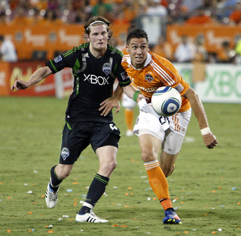 HOUSTON - JULY 30:  Geoff Cameron #20 of the Houston Dynamo fights with Erik Friberg #8 of the Seattle Sounders to gain possession of the ball at Robertson Stadium on July 30, 2011 in Houston, Texas.  (Photo by Bob Levey/Getty Images)