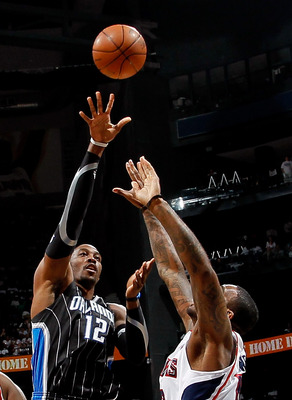 ATLANTA, GA - APRIL 24:  Dwight Howard #12 of the Orlando Magic shoots over Josh Powell #12 of the Atlanta Hawks during Game Four of the Eastern Conference Quarterfinals in the 2011 NBA Playoffs at Philips Arena on April 24, 2011 in Atlanta, Georgia.  NOT