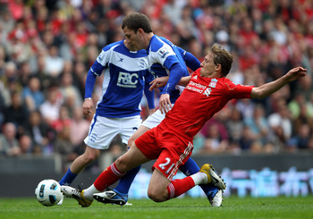 LIVERPOOL, ENGLAND - APRIL 23:  Craig Gardner of Birmingham City is tackled by Lucas of Liverpool during the Barclays Premier League match between Liverpool and Birmingham City at Anfield on April 23, 2011 in Liverpool, England. (Photo by Clive Brunskill/