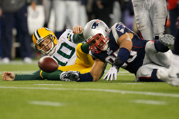 FOXBORO, MA - DECEMBER 19:  Quarterback Matt Flynn #10 of the Green Bay Packers fights for possession of a loose ball after being sacked by linebacker Tully Banta-Cain #95 of the New England Patriots during the fourth quarter of the game at Gillette Stadi