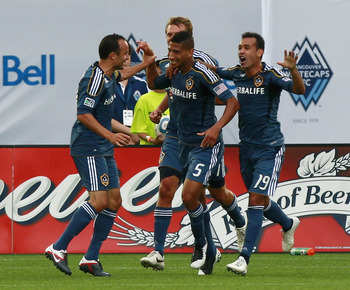 VANCOUVER, CANADA - JULY 30:  Goal-scorer Sean Franklin #5 of the Los Angeles Galaxy is congratulated by teammates Landon Donovan #10, Juninho #19 and Adam Cristman #17 during their MLS game against the Vancouver Whitecaps FC July 30, 2011 at Empire Field