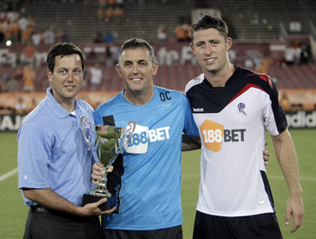 HOUSTON - JULY 20:  (L-R) Houston Dynamo President Chris Canetti presents the Charities Cup to Owen Coyle and Gary Cahill, head coach and captain of the Bolton Wanderers, after they defeated the Houston Dynamo 2-0 at Robertson Stadium on July 20, 2011 in