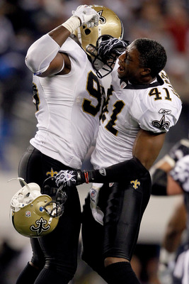 ARLINGTON, TX - NOVEMBER 25: Alex Brown #96 of the New Orleans Saints and Roman Harper #41 celebrate stopping the Dallas Cowboys in the final minute of the fourth quarter at Cowboys Stadium on November 25, 2010 in Arlington, Texas.  (Photo by Matthew Stoc