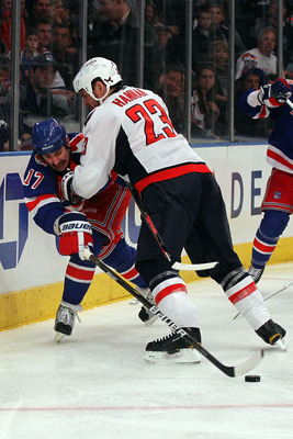 NEW YORK, NY - APRIL 17: Brandon Dubinsky #17 of the New York Rangers attempts to control the puck against Scott Hannan #23 of the Washington Capitals in Game Three of the Eastern Conference Quarterfinals during the 2011 NHL Stanley Cup Playoffs at Madiso