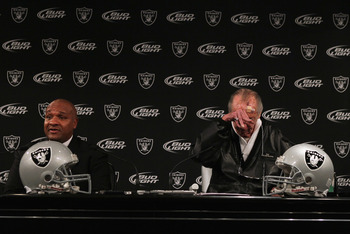 ALAMEDA, CA - JANUARY 18:  New Oakland Raiders coach Hue Jackson (L) speaks to reporters as  Raiders owner Al Davis rubs his head during a press conference on January 18, 2011 in Alameda, California. Hue Jackson was introduced as the new coach of the Oakl