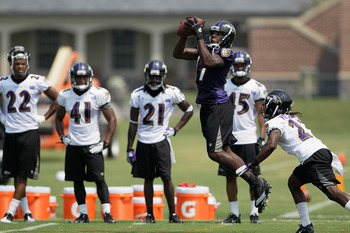 OWINGS MILLS, MD - JULY 29: Wide reciever Marcus Smith #11 makes a catch in front of defender Josh Victorian #23 of the Baltimore Ravens during training camp on July 29, 2011 in Owings Mills, Maryland.  (Photo by Rob Carr/Getty Images)