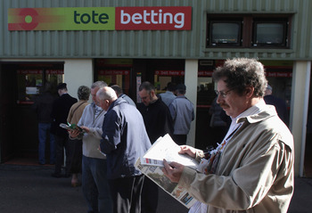 SALISBURY, ENGLAND - OCTOBER 12: Racegoers outside a Tote betting window before the 1st Race run at Salisbury Racecourse on October 12, 2009 in Salisbury, England. Prime Minister Gordon Brown is expected to announce the sale of GBP £16 billion worth of go
