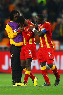 JOHANNESBURG, SOUTH AFRICA - JULY 02:  Asamoah Gyan of Ghana is consoled by John Mensah  after his team are knocked out in a penalty shoot out during the 2010 FIFA World Cup South Africa Quarter Final match between Uruguay and Ghana at the Soccer City sta