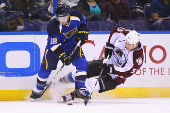 ST. LOUIS, MO - FEBRUARY 22: Kevin Shattenkirk #12 of the St. Louis Blues looks to control the puck against Cody McLeod #55 of the Colorado Avalanche at the Scottrade Center on February 22, 2011 in St. Louis, Missouri.  (Photo by Dilip Vishwanat/Getty Ima
