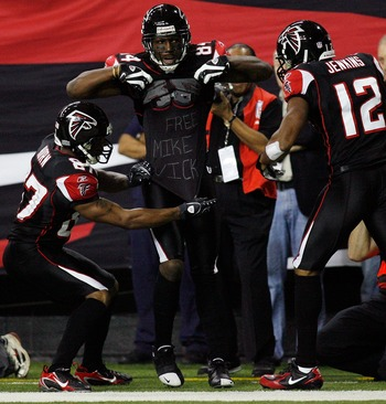 ATLANTA - DECEMBER 10:  Roddy White #84 celebrates after a touchdown with a t-shirt that reads 'Free Mike Vick' with Joe Horn #87 and Michael Jenkins #12 of the Atlanta Falcons against the New Orleans Saints on December 10, 2007 at the Georgia Dome in Atl