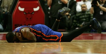 CHICAGO - JANUARY 18: Eddy Curry #34 of the New York Knicks rolls on the court after being injured diving for a loose ball against the Chicxago Bulls on January 18, 2006 at the United Center in Chicago, Illinois. The Bulls defeated the Knicks 106-104 in o