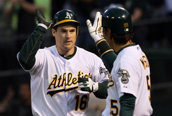 OAKLAND, CA - APRIL 01:  Josh Willingham #16 of the Oakland Athletics is congratulated by Hideki Matsui #55 after hitting a two-run home run during the first inning against the Seattle Mariners at the Oakland-Alameda County Coliseum on April 1, 2011 in Oa