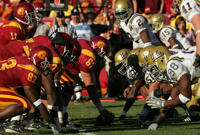 LOS ANGELES, CA - DECEMBER 03:  Matt Leinart (L) #11 of the USC Trojans stands under center Ryan Kalil #67 at the line of scrimmage against the UCLA Bruins defense  December 3, 2005 at the Los Angeles Memorial Coliseum in Los Angeles, California. USC won