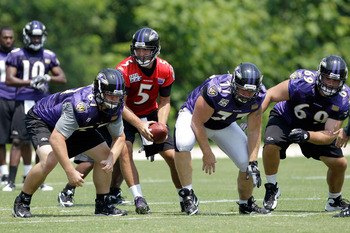 OWINGS MILLS, MD - JULY 29: Quarterback Joe Flacco #5 of the Baltimore Ravens takes a snap during training camp on July 29, 2011 in Owings Mills, Maryland.  (Photo by Rob Carr/Getty Images)