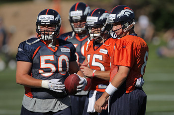 ENGLEWOOD, CO - JULY 28:  (L-R) Center J.D. Walton #50, quarterback Tim Tebow #15 and quarterback Kyle Orton #8 of the Denver Broncos take part in training camp at the Paul D. Bowlen Memorial Broncos Centre at Dove Valley on July 28, 2011 in Englewood, Co