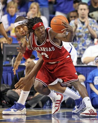 LEXINGTON, KY - JANUARY 23:  DeMarcus Cousins #15 of the Kentucky Wildcats and Courtney Fortson #4 of the Arkansas Razorbacks reach for a loose ball during the SEC game on January 23, 2010 at Rupp Arena in Lexington, Kentucky. Kentucky won 101-70.  (Photo