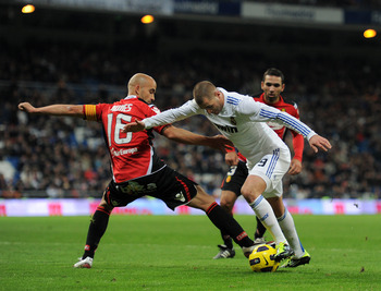 MADRID, SPAIN - JANUARY 23:  Karim Benzema (R) of Real Madrid fights for the ball with Jose Nunes of Mallorca during the la liga match between Real Madrid and Mallorca at Estadio Santiago Bernabeu on January  23, 2011 in Madrid, Spain.  (Photo by Jasper J