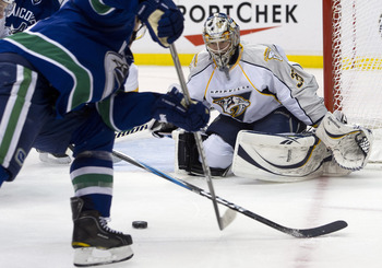 VANCOUVER, CANADA - APRIL 28: Goalie Pekka Rinne #35 of the Nashville Predators keeps and eye of the puck as Daniel Sedin #22 of the Vancouver Canucks tries to shoot during the second period in Game One of the Western Conference Semifinals during the 2011