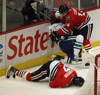 CHICAGO, IL - APRIL 17: Chris Campoli #14 of the Chicago Blackhawks hits Raffi Torres #13 of the Vancouver Canucks after Torres knocked down Brent Seabrook #7 with a hit behind the net in Game Three of the Western Conference Quarterfinals during the 2011