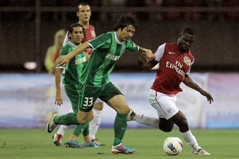 HANGZHOU, CHINA - JULY 16: Emmanuel Frimpong (R) of Arsenal battles for the ball with Wang Song of Hangzhou Greentown during the pre-season friendly match between Hangzhou Greentown and Arsenal at Yiwu Meihu Stadium on July 16, 2011 in Hangzhou, China.(Ph