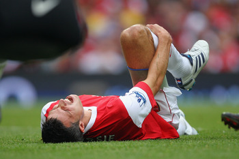 LONDON, ENGLAND - AUGUST 21:  Robin van Persie of Arsenal holds his leg after a tackle during the Barclays Premier League match between Arsenal and Blackpool at The Emirates Stadium on August 21, 2010 in London, England.  (Photo by Clive Rose/Getty Images