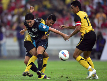 KUALA LUMPUR, MALAYSIA - JULY 13: Samir Nasri of Arsenal is challenged by Mohd Azmi Muslim #11 and Ahmad Fakri of Malaysia during the pre-season Asian Tour friendly match between Malaysia and Arsenal, at Bukit Jalil National Stadium on July 13, 2011 in Ku