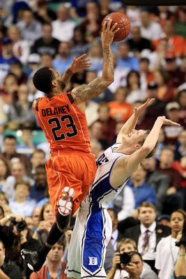 GREENSBORO, NC - MARCH 12:  Malcolm Delaney #23 of the Virginia Tech Hokies shoots against Kyle Singler #12 of the Duke Blue Devils during the first half in the semifinals of the 2011 ACC men's basketball tournament at the Greensboro Coliseum on March 12,
