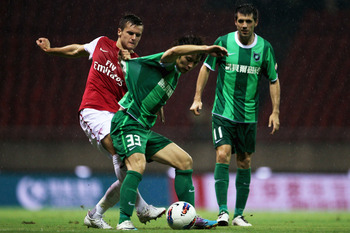 HANGZHOU, CHINA - JULY 16: Carl Jenkinson (L) of Arsenal battles for the ball with Wang Song of Hangzhou Greentown during the pre-season friendly match between Hangzhou Greentown and Arsenal at Yiwu Meihu Stadium on July 16, 2011 in Hangzhou, China. (Phot